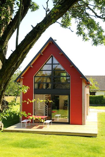 red A-frame house in a beautiful garden setting