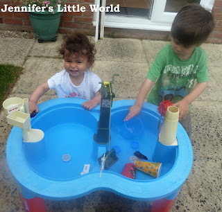 Children playing at water table in the garden