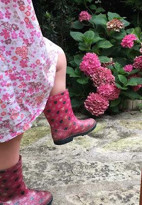 deux bottes d'enfant en mouvement devant l'hortensia