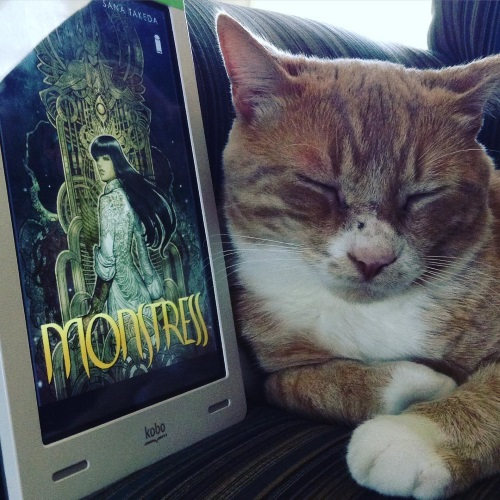 A ginger cat with white paws and a white belly curls up against a white Kobo with Monstress's cover on its screen. The cover features a long-haired girl of Asian descent, twisted to look at something over her left shoulder. An airy, abstract golden structure rises behind her.