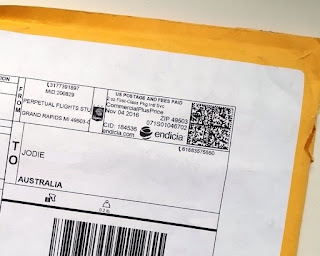 The yellow large envelope in which the pin was posted. The white label has black printing on it including a QR code at the top right where a stamp would normally be and a barcode on the bottom of the picture.