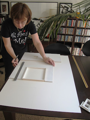 Woman tracing dolls' house kit walls onto of a large piece of mat board.