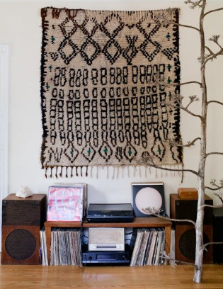 Hanging a rug on the living room wall can be a creative way to embellish the appearance of a plain wall.
