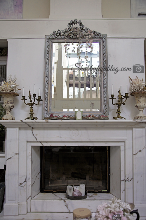 A French farmhouse style mantel display; marble fireplace, brass candelabras and an intricate white wood mirror with a stunning hand-carved wooden frame.