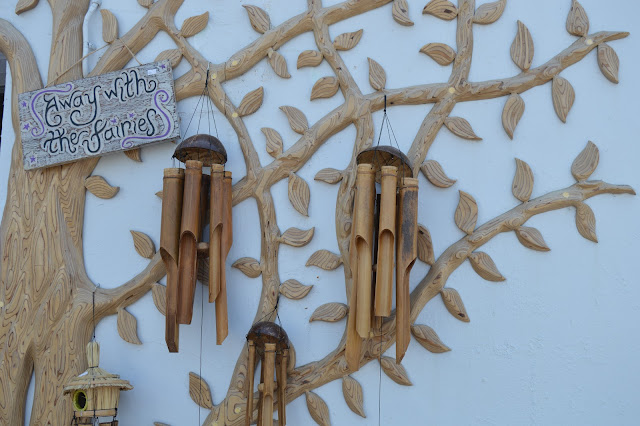 A tree sculpted onto a wall with wind chimes everywhere.