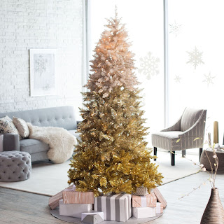 An ombre Christmas tree in shades of gold sitting in a grey and beige living room