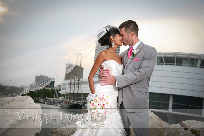 Groom kissing bride with long flowing veil near Discovery World
