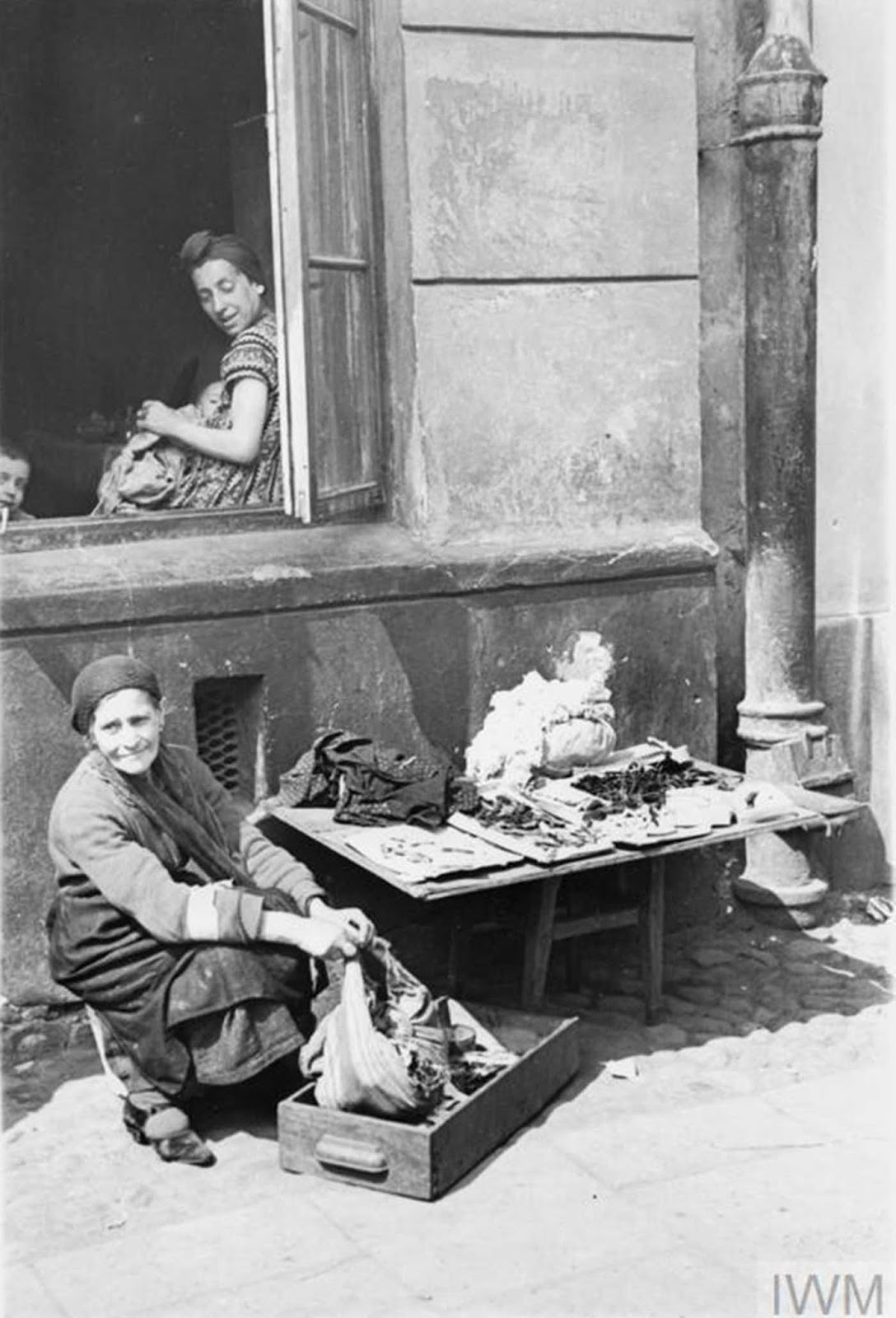 An elderly Jewish woman selling her scarce possessions in the street of the ghetto.