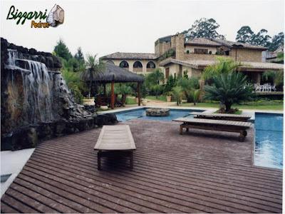 Construção da cascata em piscina com pedras ornamentais com execução do deck de madeira e a execução do paisagismo.