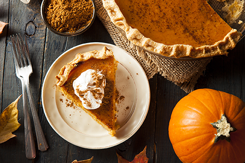 image of a rustic dining table with servings of pumpkin pie, a bowl of cinnamon and fall leaves