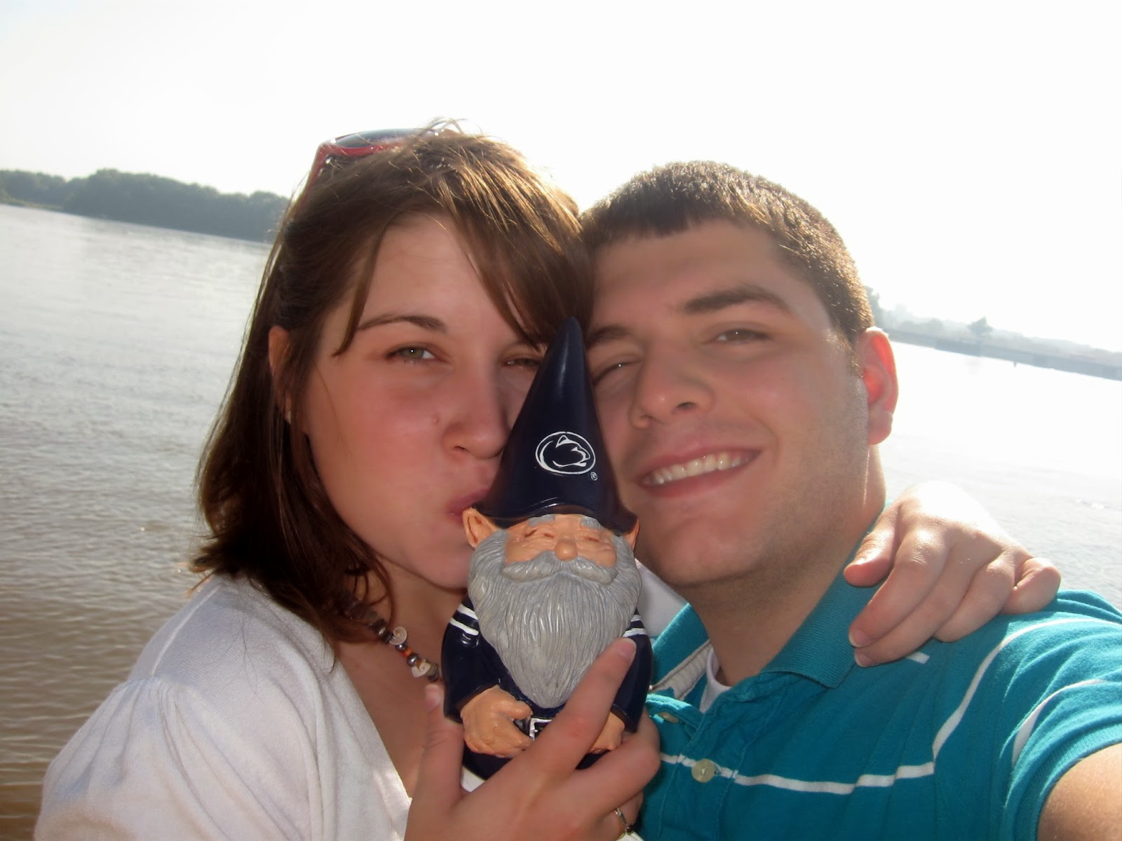 couple with their penn state gnome in front of the mississippi river