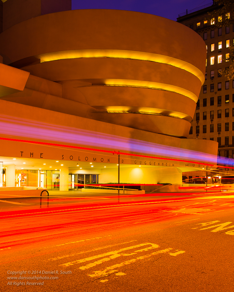 a photo of the guggenheim museum new york at night with traffic trails