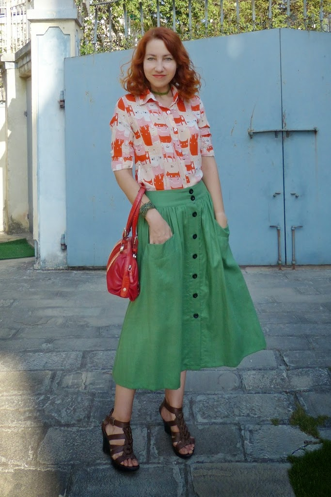 Orange cats blouse worn with green button down skirt