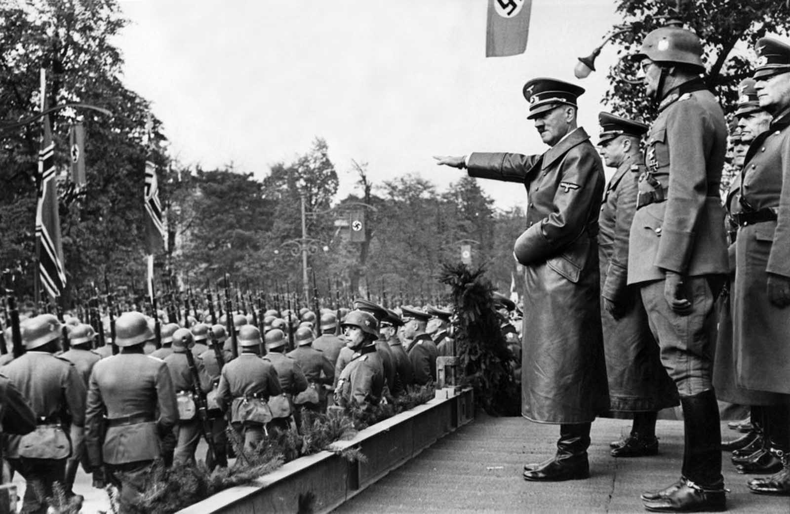 Adolf Hitler salutes parading troops of the German Wehrmacht in Warsaw, Poland, on October 5, 1939 after the German invasion. Behind Hitler are, from left to right: Colonel General Walther von Brauchitsch, Lieutenant General Friedrich von Cochenhausen, Colonel General Gerd von Rundstedt, and Colonel General Wilhelm Keitel.