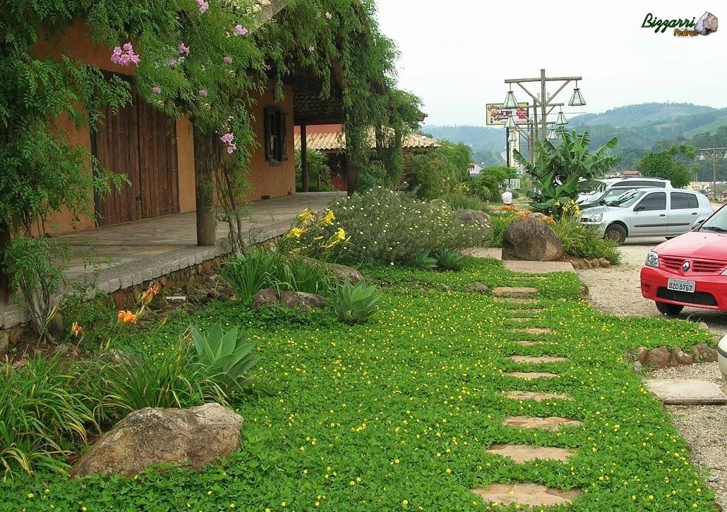 Caminho no jardim com pedra moledo chapada com a execução do paisagismo com as pedras ornamentais e o gramado com grama amendoim.