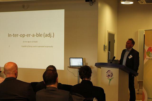 """fotografía de una presentación con un señor en un atril y una diapositiva con la palabra """"interoperable"""""""