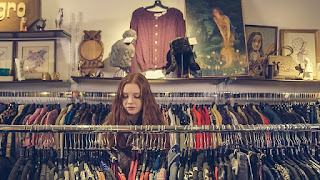 A teenage girl looking a clothes in a store.