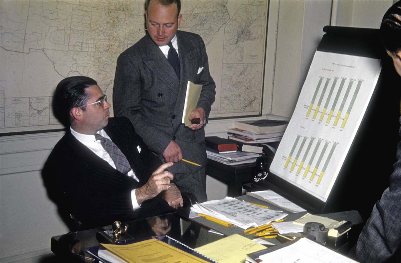 A plethora of yellow pencils litters this man's desk as he investigates detailed statistics relating to a client campaign.