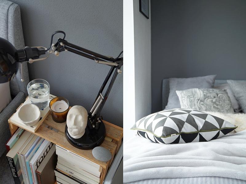 Schlafzimmer im Herbst einrichten und dekorieren in Grautönen und Weiß, mit vielen Wohntextilien für eine gemütliche Atmosphäre, Deko mit Fellen, Kissen, Decken, graues Bett mit Kopfteil, weiße und dunkelgraue Wände, Weinkiste mit Büchern als Nachttisch