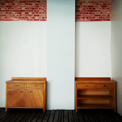 One-twelfth scale miniature scene of two work benches in an empty industrial space.