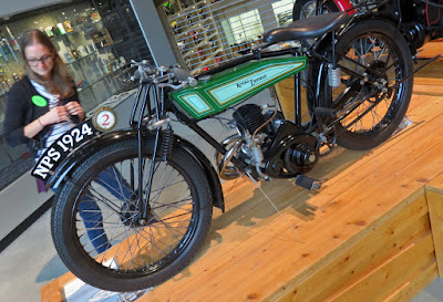 Vintage Royal Enfield motorcycle on display stand.