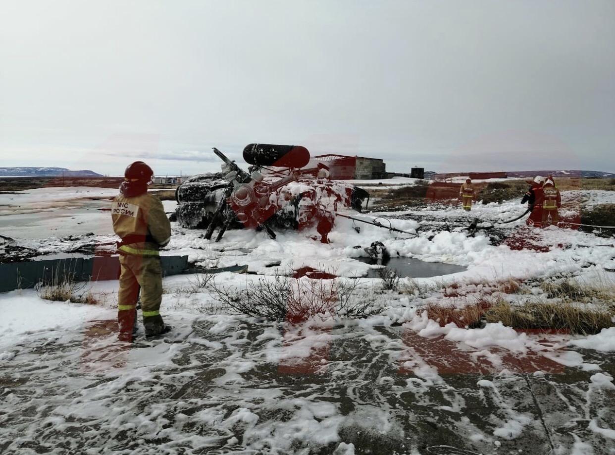 Ugunsdzēsējs skatās uz nokritušu apdegušu un apledojušu helikoptera vraku