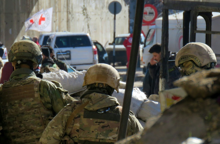 Russian soldiers gather in the government held side of the embattled city of Aleppo before the start on an evacuation operation of rebel fighters on December 15, 2016