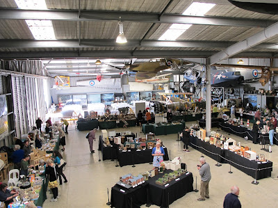 View of the sales and display hall of a miniature convention, set in a hangar.