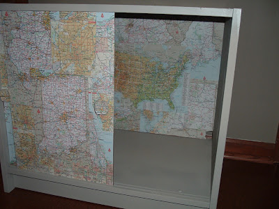 The particle board cabinet with the doors open, now painted and decoupaged with maps
