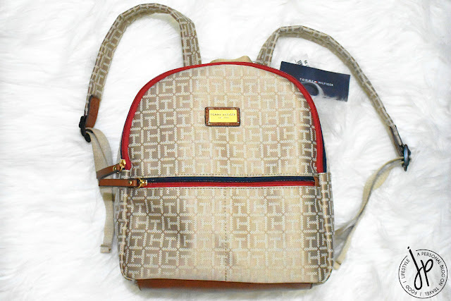 beige backpack with blue and red zipper
