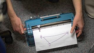 """Tiflopedagogė Adrienne Shoemaker aklai mokinei pritaiko geometrijos užduotį, naudodamasi mašinėle """"Perkins Brailler"""""""