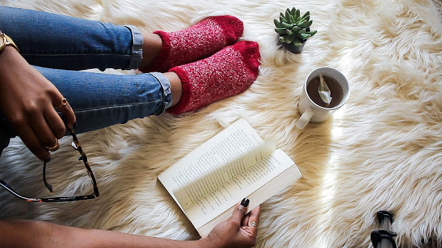 A girl with red socks is reading a book