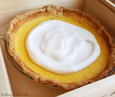 whole lemon pie with cloud of honey whipped cream in the center