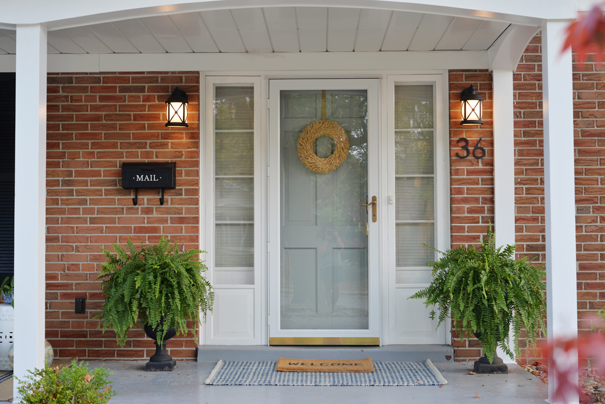 fresh traditional front porch decor with layered rugs and blue grey painted front door