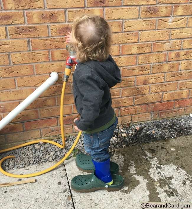 toddler wearing adult shoes and trying to turn on tap