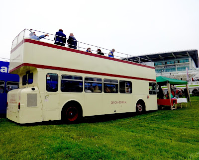 A cream and red, double decker bus parked near the race course in Epsom