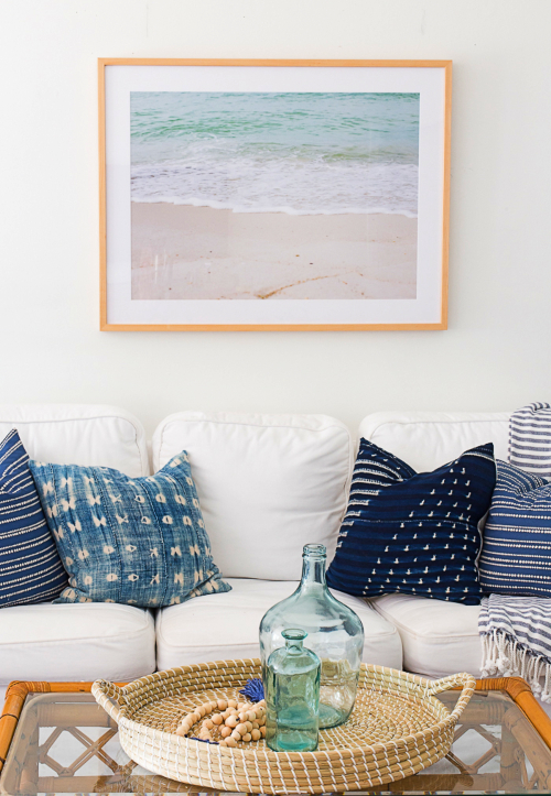 Framed Ocean Wave Beach Photograph above Sofa in Living Room