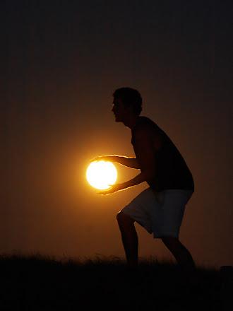 Güneşi bir basketbol topu gibi tutan sporcu