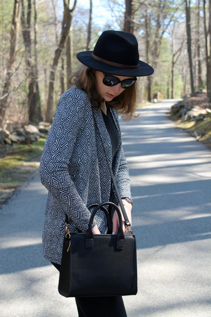 patterned black and white jacket and black bag