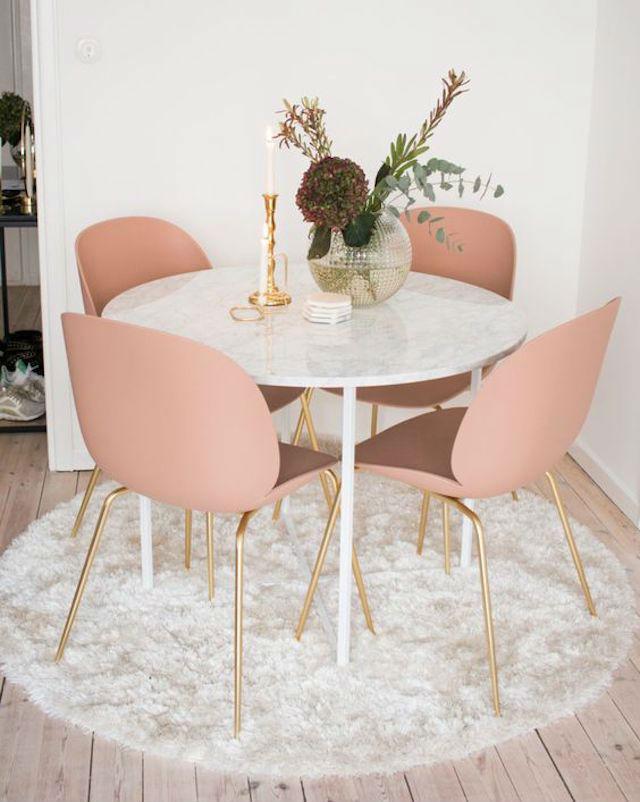 Mesa redonda con tapa de mármol, con sillas color rosa maquillaje con patas doradas