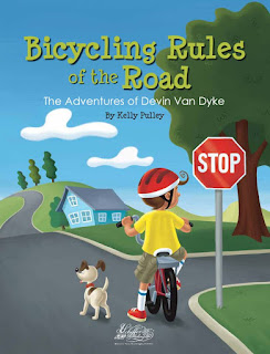 Book cover, 'Bicycling Rules of the Road' by Kelly Pulley. Image depicts boy in helmet on his bicycle, shown from the rear view, paused in a roadway next to a stop sign. The boy's head is turned right, looking down a side street that intersects the road he is on. The road is lined with green landscaping, a single blue house and trees. A dog stands in the road next to the boy, looking ahead.