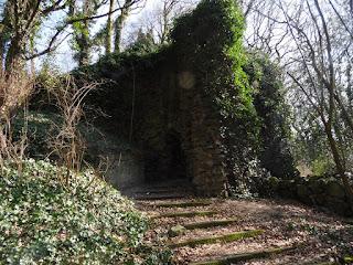 Eine alte, mit Efeu bewachsene Mauer mit einem Durchgang