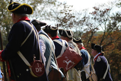 Line of Revolutionary War reenactors with backs to camera