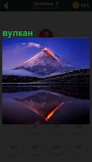 Отражение в озере высокого вулкана, из которого выходит лава