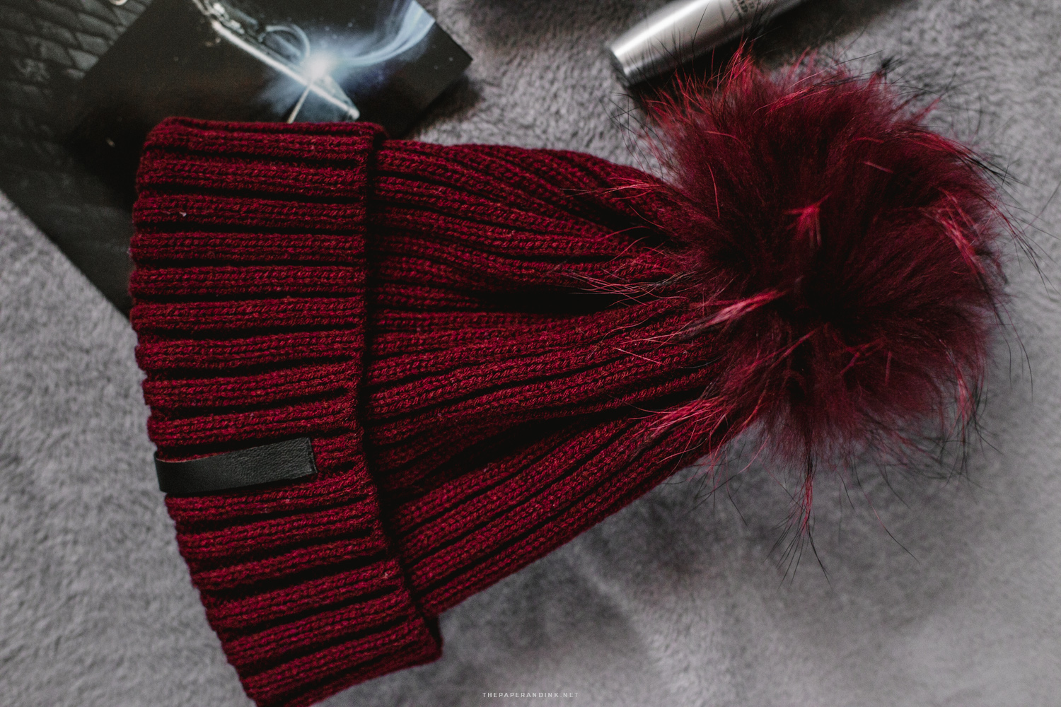 A burgundy beanie with a furry pompom by Cortefiel.