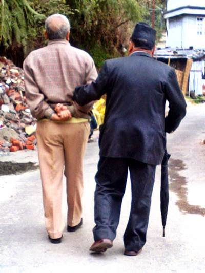 Two old men walking together arm in arm