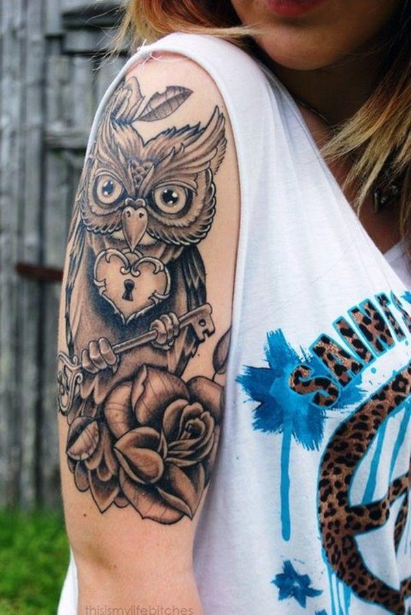 Mujer rubia con camiseta, lleva en su hombro el tatuaje de un buho que sostiene una gran llave maestra