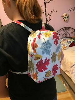 Girl wearing home-sewn mini-backpack