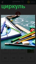 На столе лежат карандаши, тетрадь и циркуль
