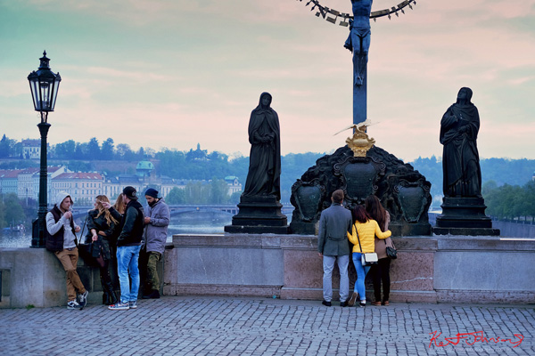 Groups of friends waiting for dawn under the statue of the Holy Crucifix and Calvary. The Charles Bridge in Spring Prague by Travel and Lifestyle Photographer Kent Johnson.